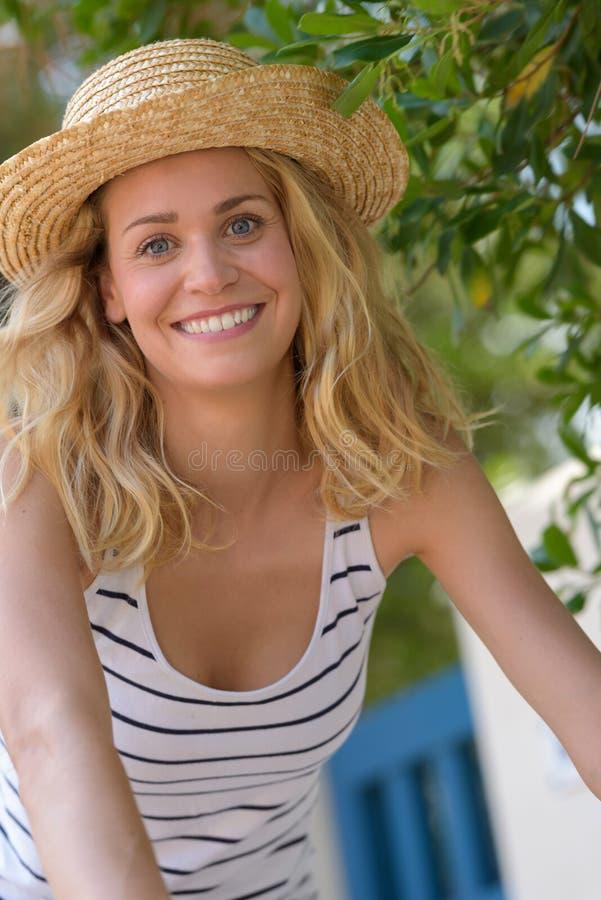 Blond kvinnlig flicka i sugrörhatt på solen royaltyfria foton