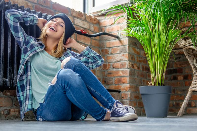 Blond kvinnlig i grov bomullstvilljeans som poserar på ett golv royaltyfri fotografi