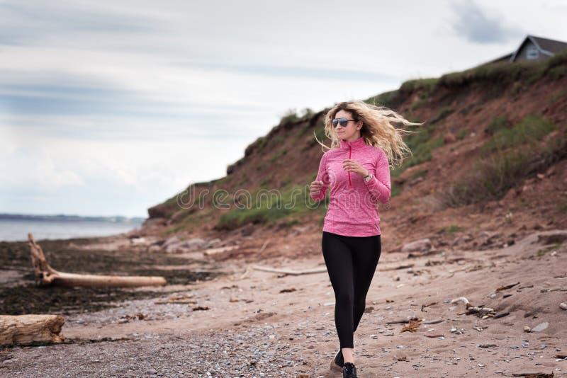 Blond kvinnlig löpare som joggar på stranden fotografering för bildbyråer