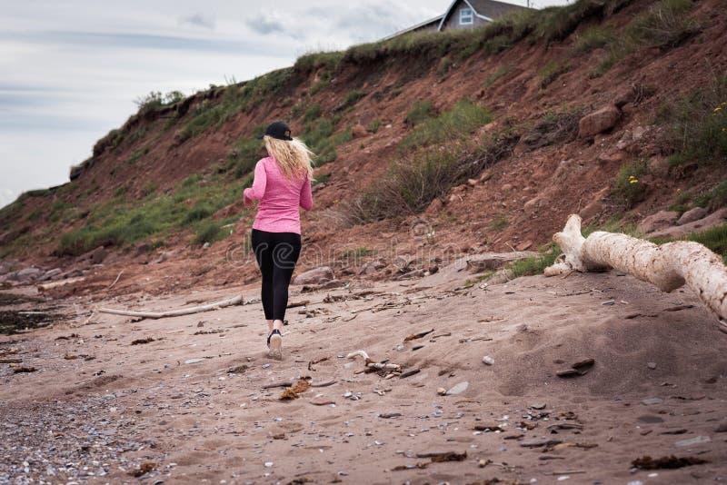 Blond kvinnlig löpare som joggar på stranden arkivbild