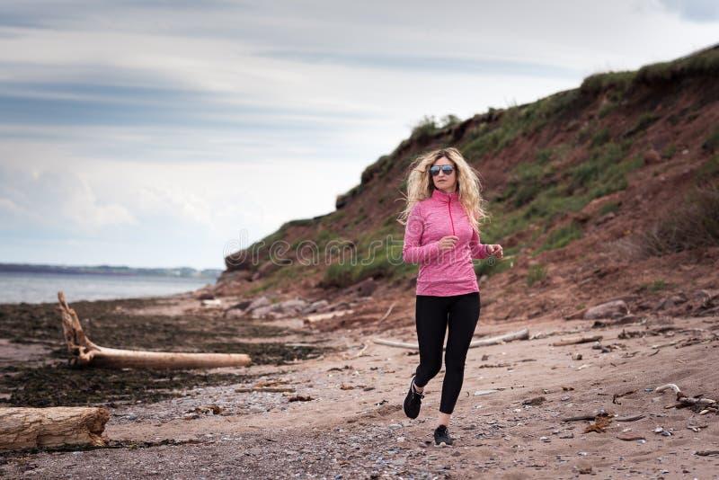 Blond kvinnlig löpare som joggar på stranden royaltyfria bilder