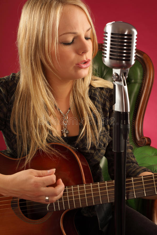 Blond kvinnlig som leker den akustiska gitarren royaltyfri foto