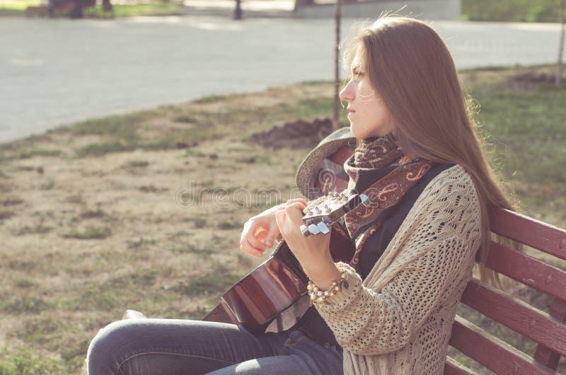 Blond långhårig flicka som spelar gitarren royaltyfria bilder