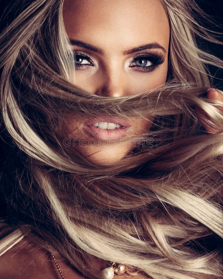 Blond lady with beautiful hair on grey royalty free stock photo