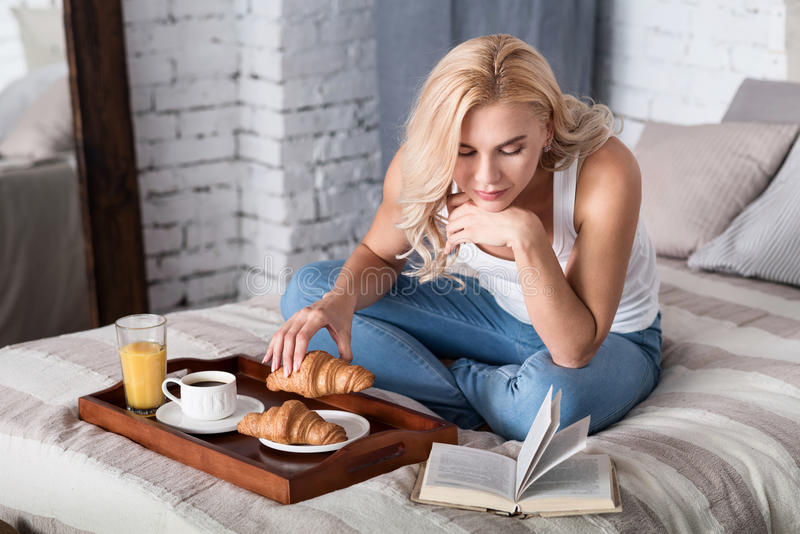 Blond lady having breakfast and reading book stock images