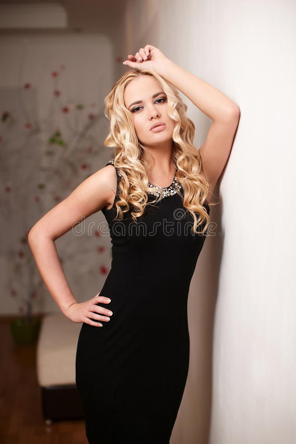 Blond Lady Model In Black Dress Standing Near Wall Royalty Free Stock Image