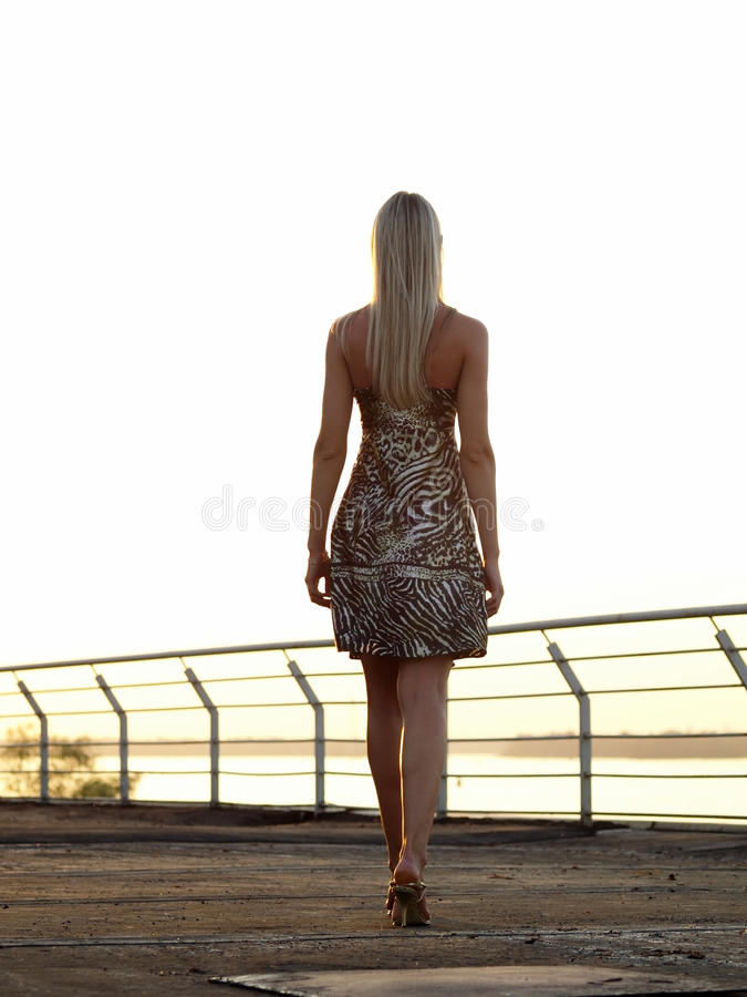 Blond lady walking over promenade royalty free stock photos
