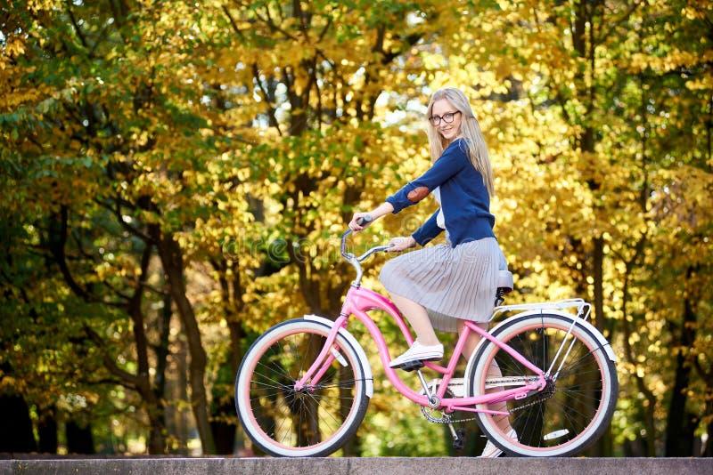 Blond langharig aantrekkelijk meisje op roze damefiets in zonnig de herfstpark op bomenachtergrond royalty-vrije stock foto