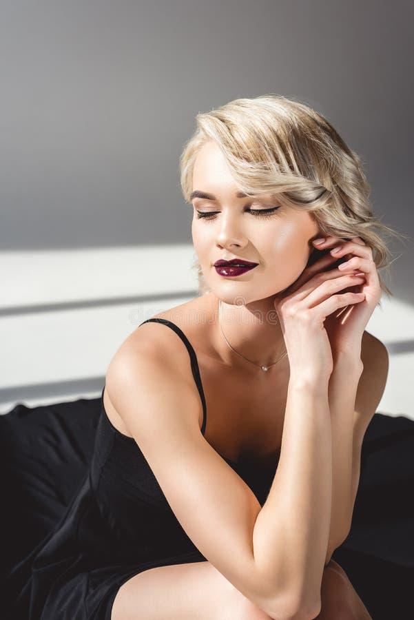blond le flicka som poserar i elegant svart klänning fotografering för bildbyråer