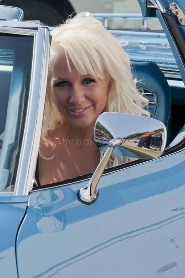 Blond le kvinna i en bil arkivfoton