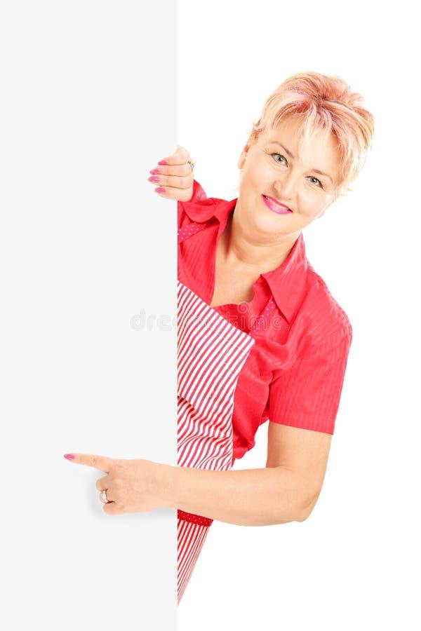Blond le kvinna som bär ett förkläde och gör en gest på en panel fotografering för bildbyråer
