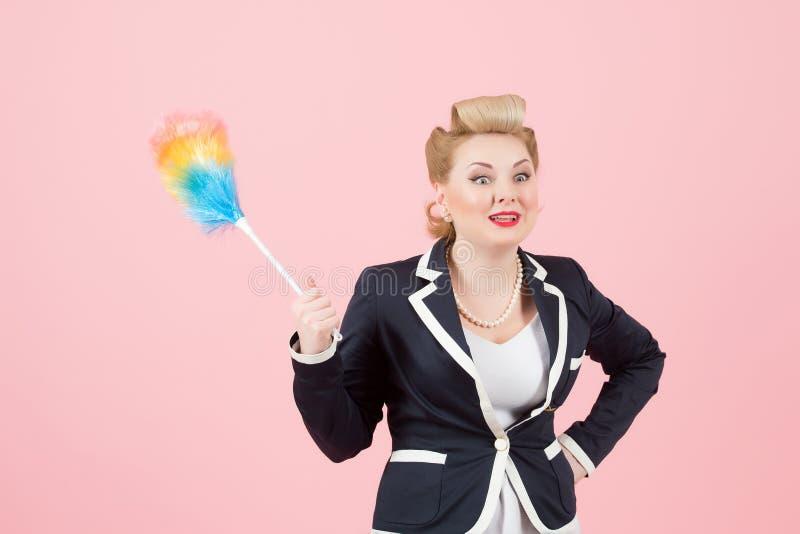 Blond likformig för kvinna i regeringsställning med den kulöra dammtrasan i hand- och framsidauttryck En flicka i omslag med damm royaltyfria foton