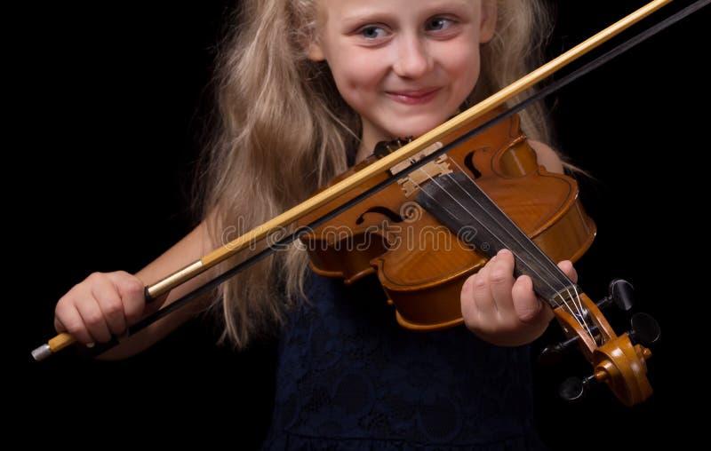 Blond liten flicka som lär att spela fiolen på svart royaltyfria foton