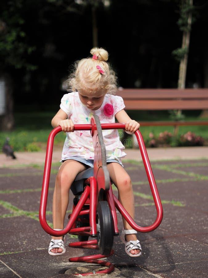 Blond liten flicka som spelar i lekplatsen arkivfoton