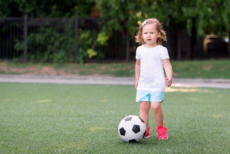 Blond litet barnflicka i blåa kortslutningar och rosa gymnastikskor som spelar med fotbollbollen på det fria för fotbollfält elle arkivfoton