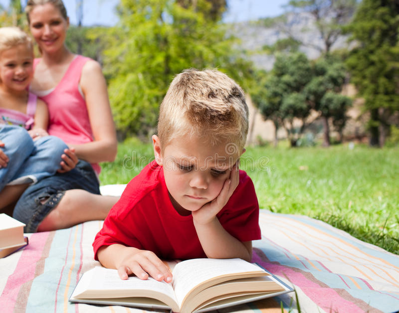 Blond Little Boy Reading At A Picnic Stock Images