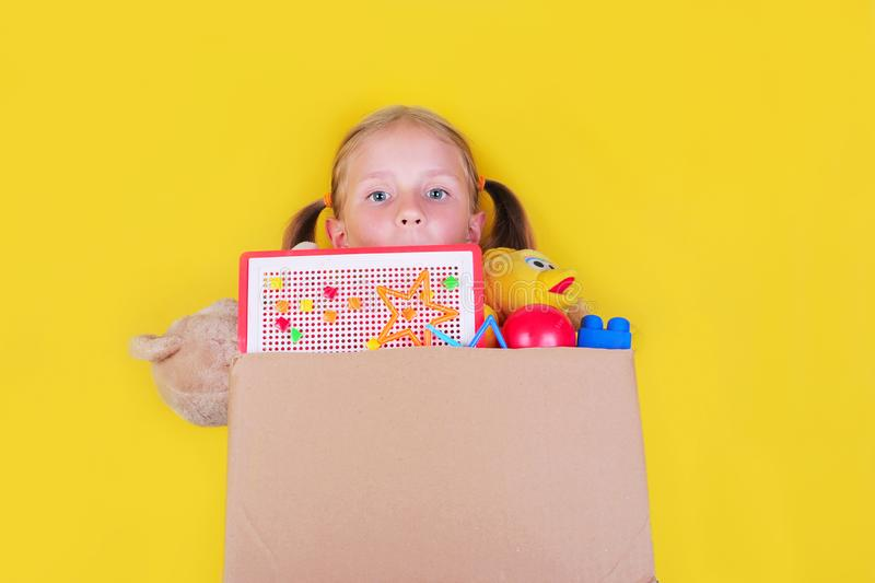 Blond little girl holding a box with toys on yellow background. Donation concept.. royalty free stock images