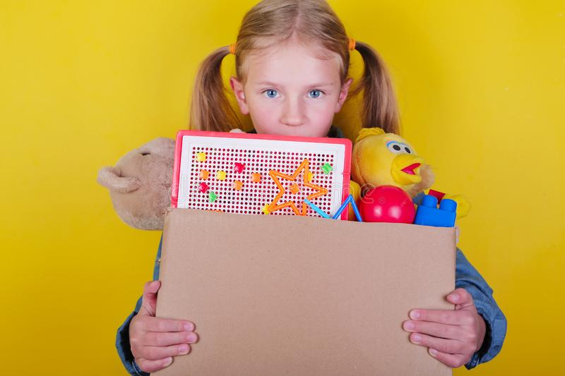 Blond little girl holding a box with toys on yellow background. Donation concept.. royalty free stock photo