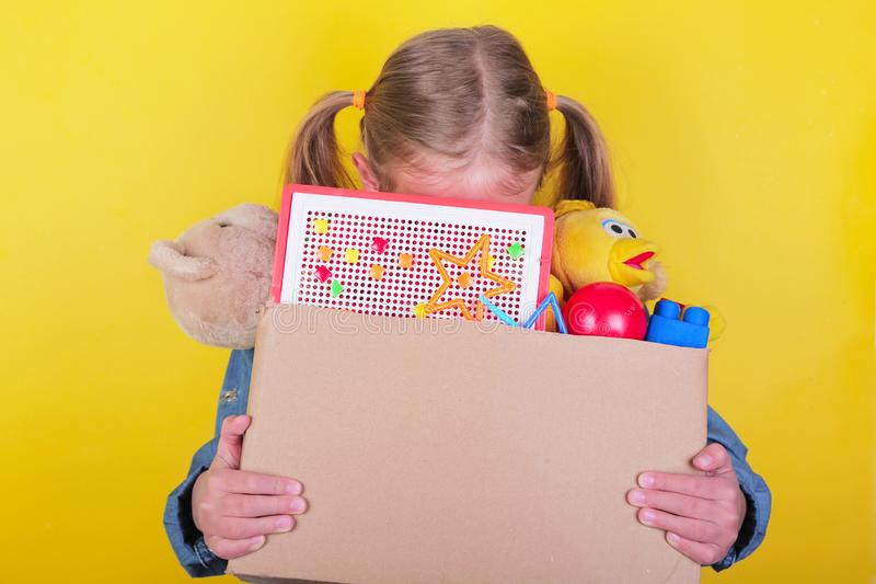 Blond little girl holding a box with toys on yellow background. Donation concept.. stock image
