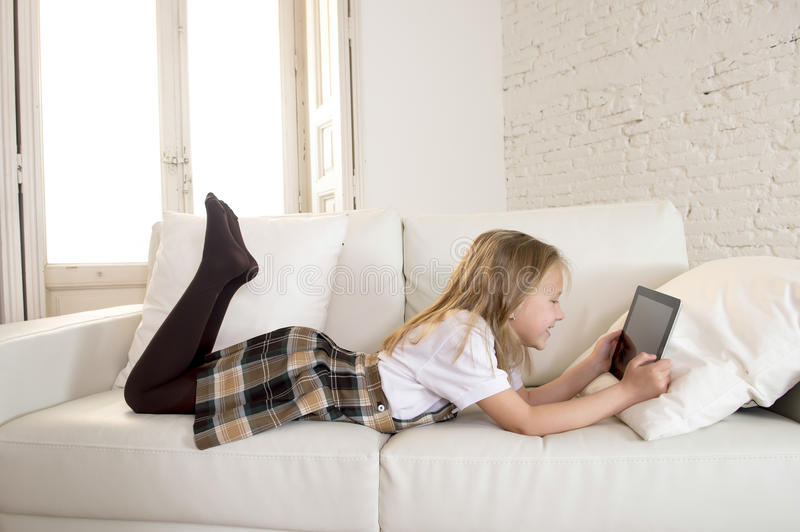 Blond little girl lying on home sofa couch using internet app on digital tablet pad on digital tablet pad. Young sweet cute and beautiful 6 or 7 years old girl stock images