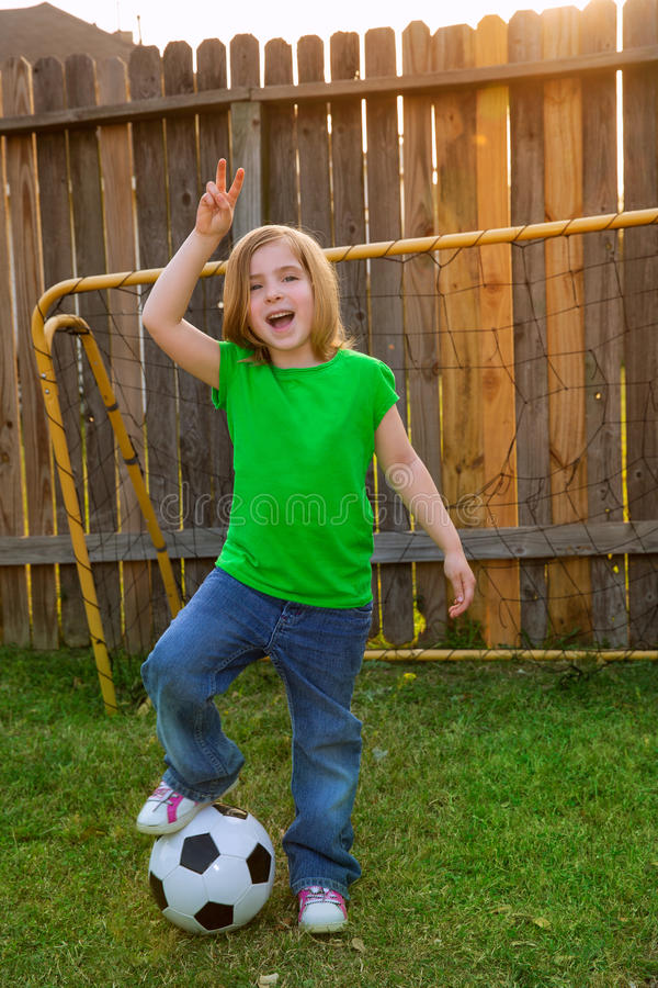 Blond little girl soccer player happy in backyard. With ball stock photography