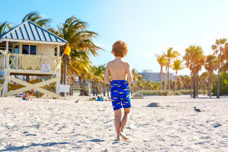Blond little kid boy having fun on Miami beach, Key Biscayne. Happy healthy cute child playing with sand and running stock photography
