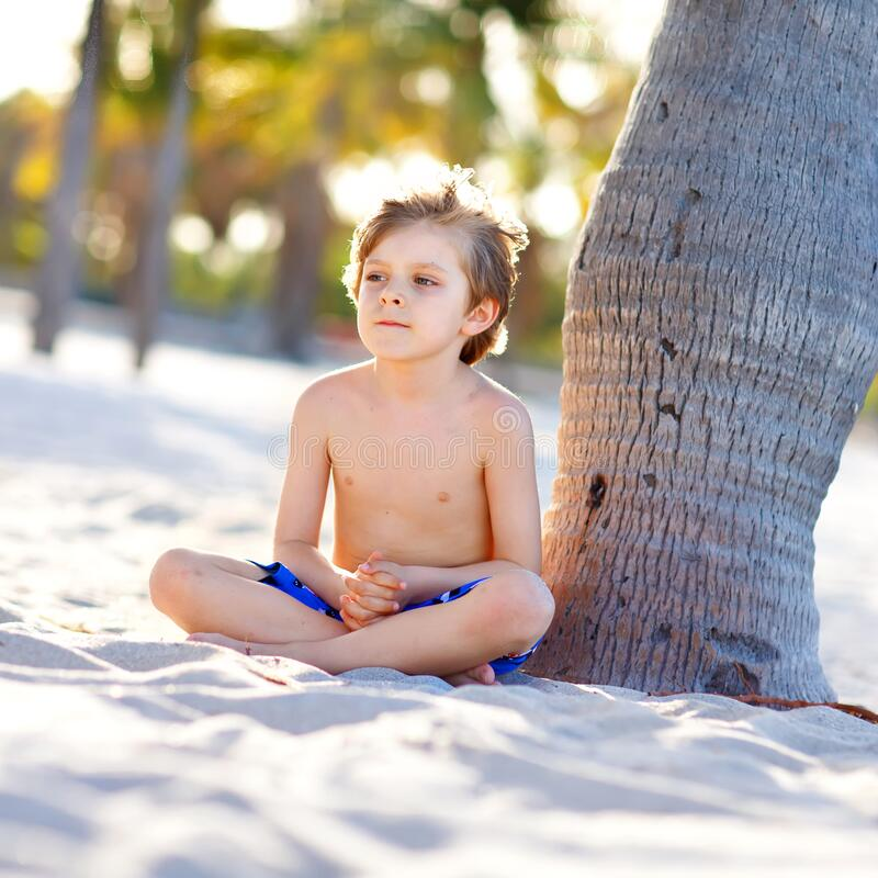 Blond little kid boy having fun on Miami beach, Key Biscayne. Happy healthy cute child playing with sand and running stock photos