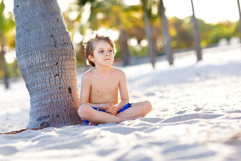Blond little kid boy having fun on Miami beach, Key Biscayne. Happy healthy cute child playing with sand and running stock images