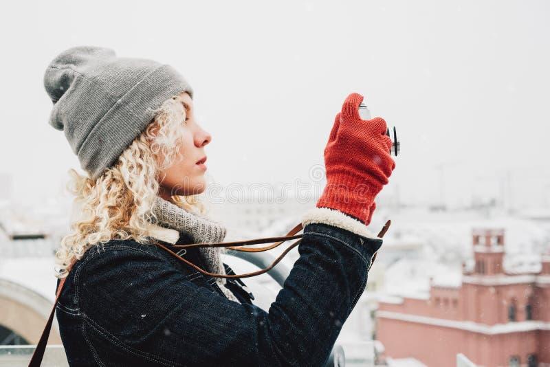 Blond lockig flickaskytte på filmfotokamera, vinter royaltyfria bilder