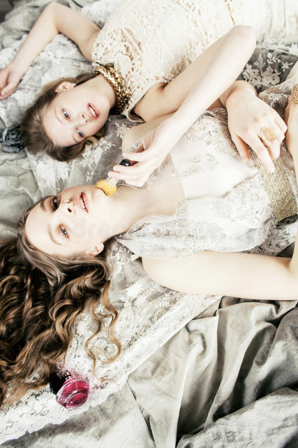 Blond lockig frisyrflicka för nätt tvilling- syster två i lyxig husinre tillsammans, rikt ungdomarbegrepp arkivfoton