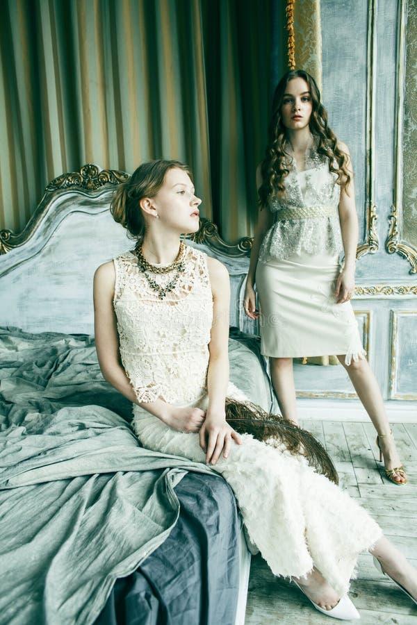 Blond lockig frisyrflicka f?r n?tt tvilling- syster tv? i lyxig husinre tillsammans, rikt ungdomarbegrepp royaltyfri bild