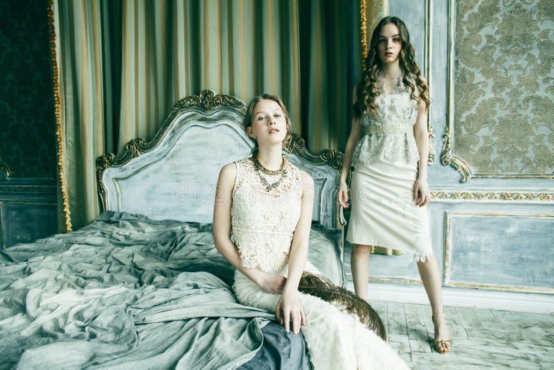 Blond lockig frisyrflicka f?r n?tt tvilling- syster tv? i lyxig husinre tillsammans, rikt ungdomarbegrepp royaltyfri foto