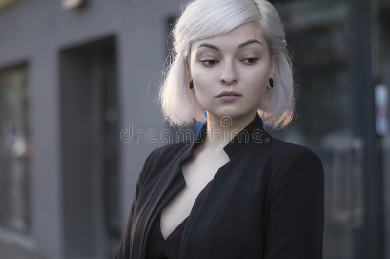Blond lovely model in sunset light outdoors closeup portrait in black suit and with ear tunnels. no makeup perfect skin. royalty free stock photo
