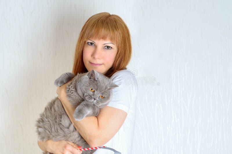 Blond lub czerwonego włosy dojrzały starszy żeński relaksujący w domu trzyma i huging ślicznego mruczeć kota zdjęcie royalty free