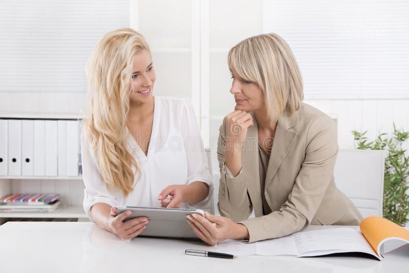 Blond lyckad attraktiv affärskvinna som två arbetar i ett lag arkivfoto