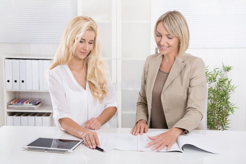Blond lyckad attraktiv affärskvinna som två arbetar i ett lag royaltyfria foton