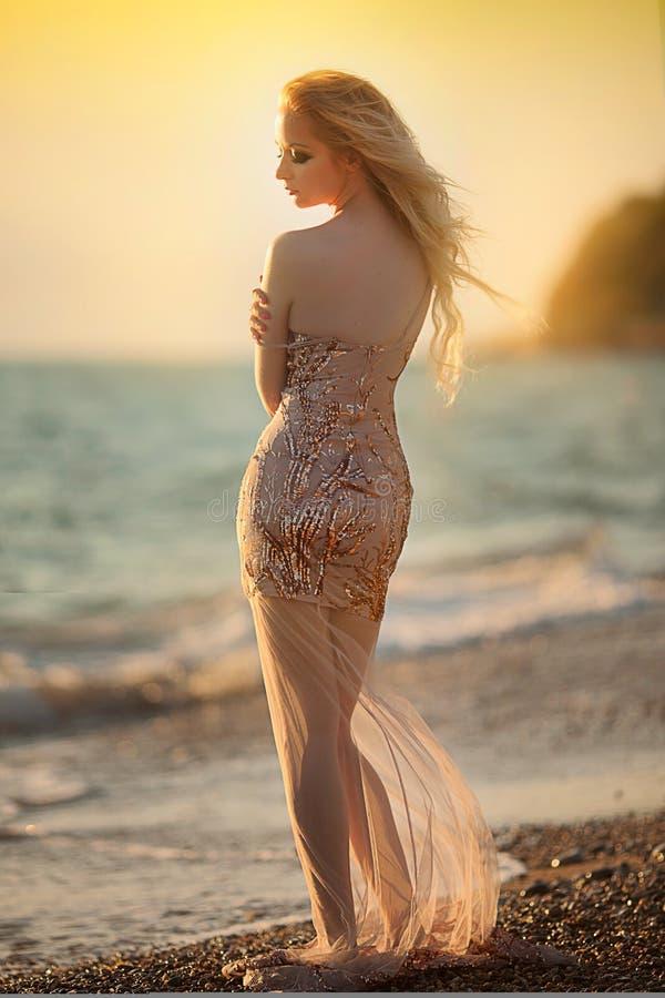 Blond młoda kobieta model z jaskrawym makeup outdoors modnym stylem w wieczór sukni za niebieskim niebem obraz stock