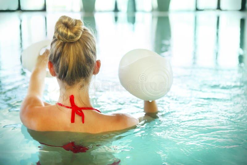 Blond młoda kobieta robi aqua aerobikom z dumbbells w dopłynięciu obraz royalty free