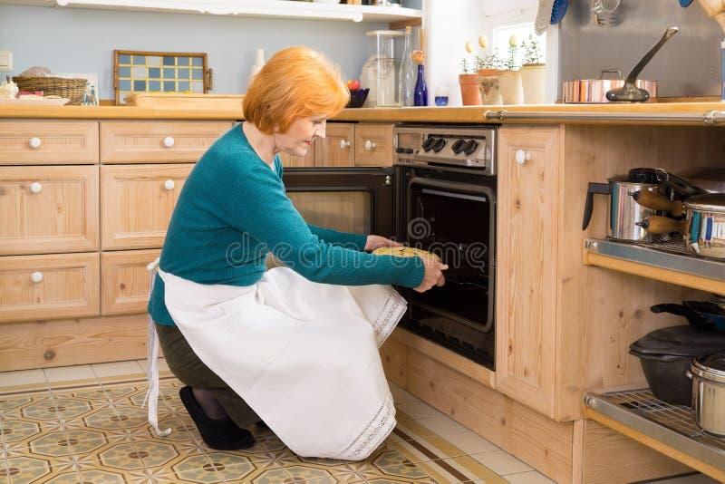 Blond mama Stawia tort w piekarniku Z fartuchem zdjęcie stock