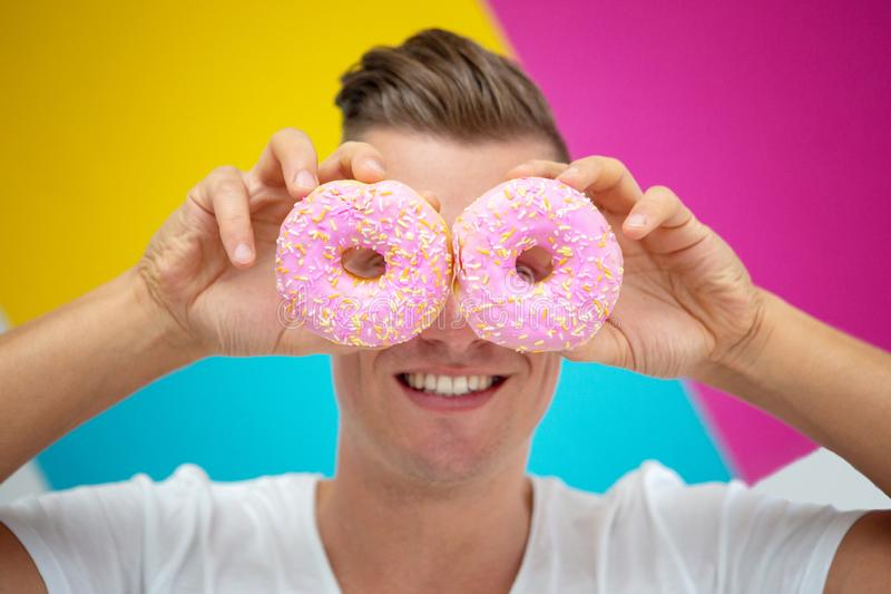 blond man holding two pink donuts in front of colorful background royalty free stock image