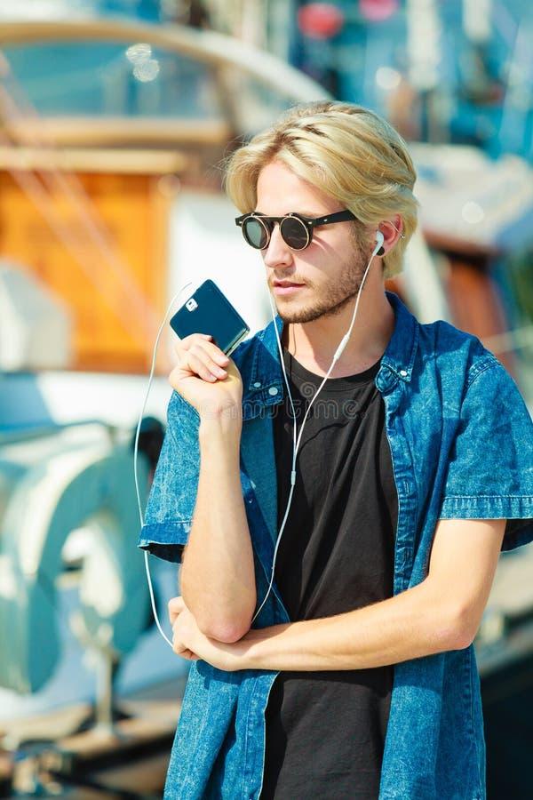 Blond man i solglasögon som lyssnar till musik arkivbild