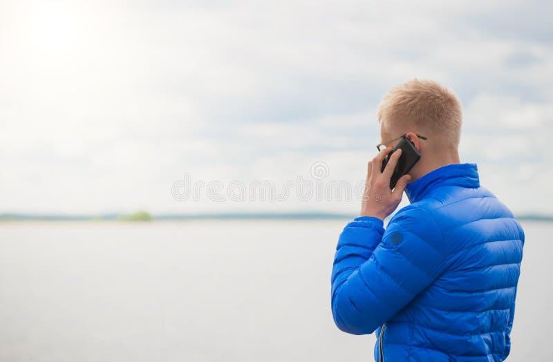 Blond man som använder mobiltelefonen på sjön arkivbilder