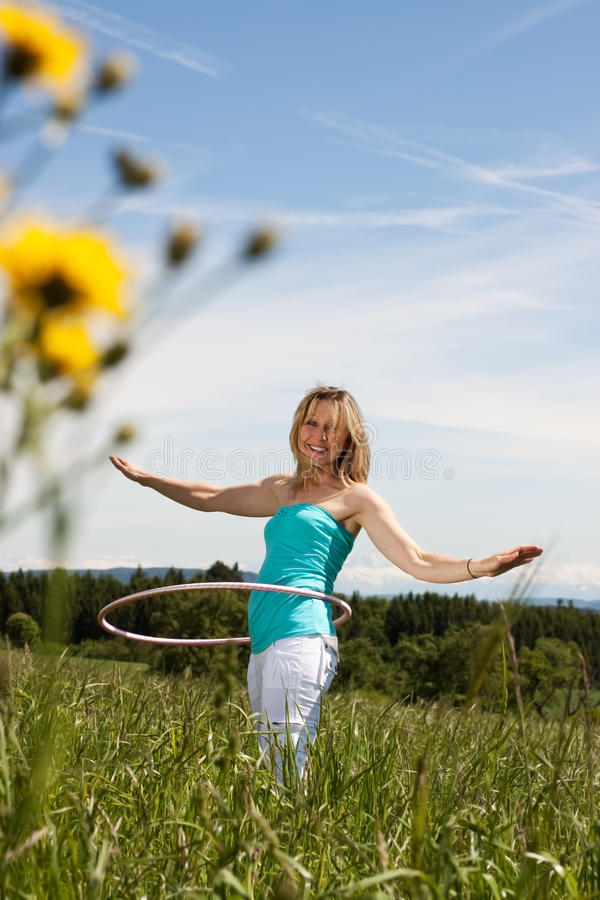 Blond mature woman exercises with hula hoop. Young woman standing on a lawn and trained with hula hoops. In the background the Alps stock photography