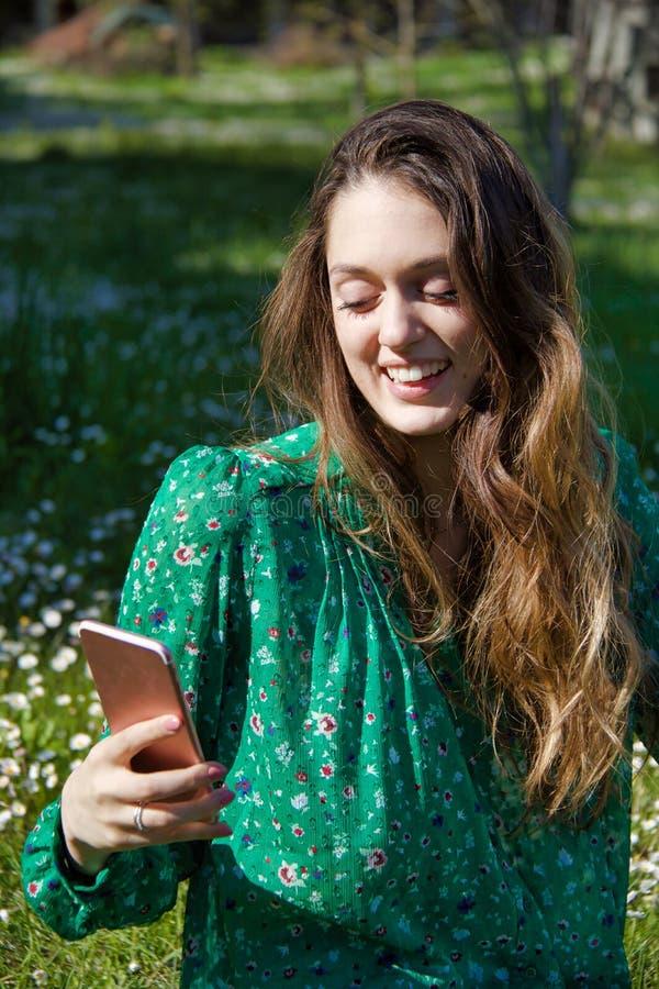 Blond meisje in de tuin die gebruikend mobiele telefoon glimlachen royalty-vrije stock foto's