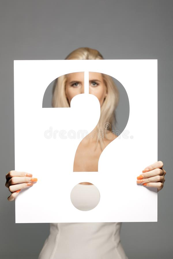 Blond meisje die een vraagtekenteken houden stock afbeeldingen