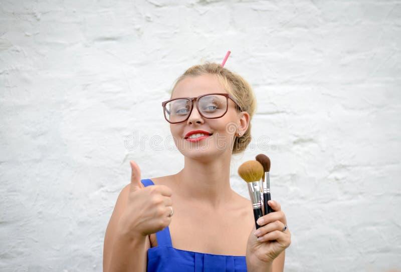 Blond meisje die in hipsterglazen met make-up beduimelen royalty-vrije stock foto's