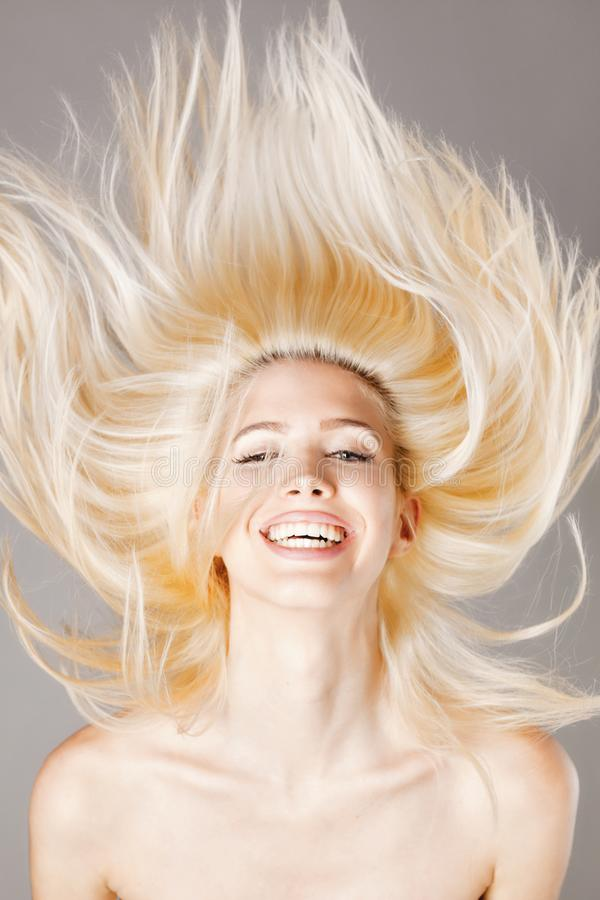 Blond meisje die met haar in de lucht glimlachen royalty-vrije stock afbeeldingen