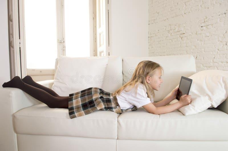 Blond meisje die op de laag liggen die van de huisbank Internet app op digitaal tabletstootkussen gebruiken op digitaal tabletsto stock afbeelding