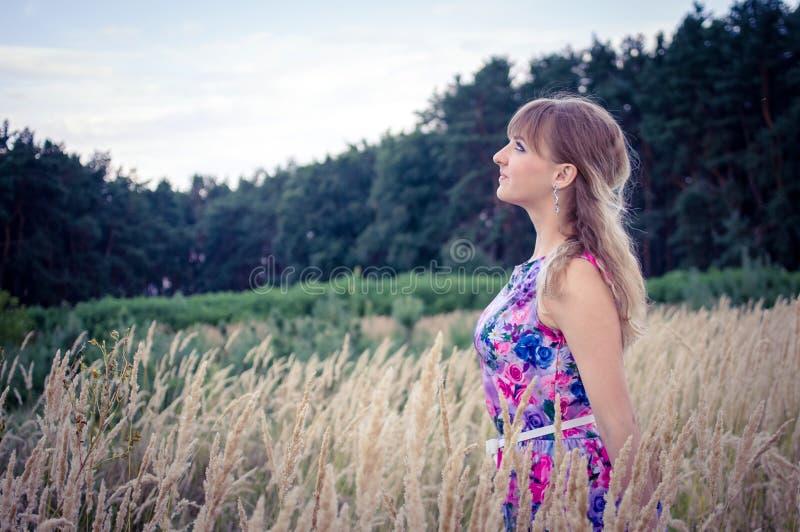 Blond meisje die zich in de tarwe bevinden royalty-vrije stock foto's
