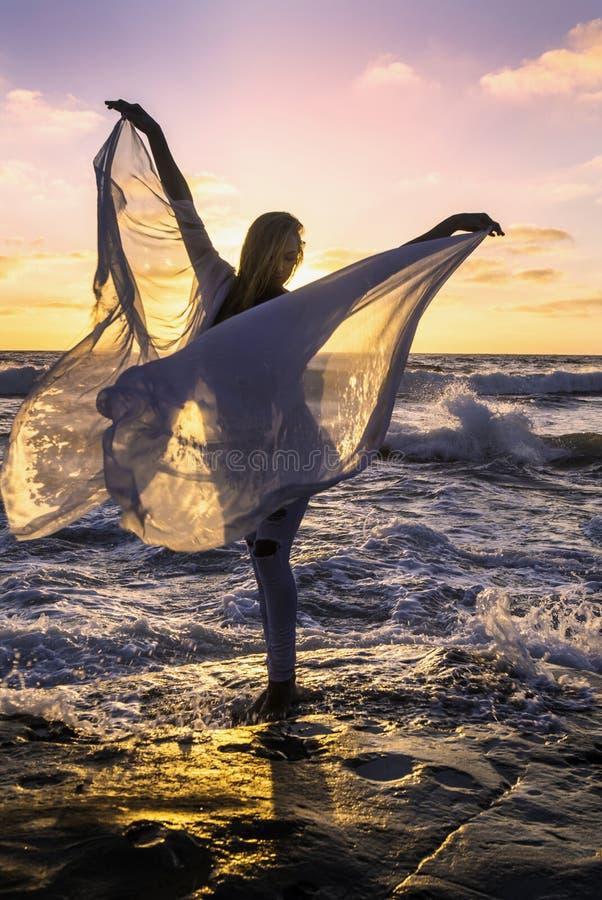 Blond meisje door de oceaan stock fotografie